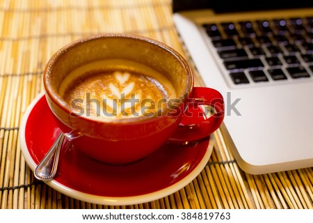 Hot latte coffee in a red cup with laptop - stock photo