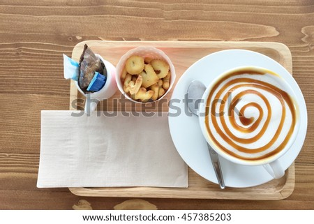 Hot Latte coffee in white dish cup,  biscuits cracker and sugar on wood table.Top view. - stock photo