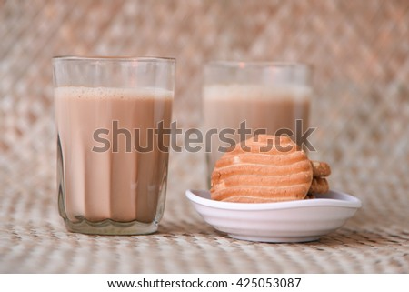 Hot masala tea / masala chai / Teh Tarik and biscuit, Kerala India. Evening tea with refreshing Indian blend of black tea with milk and spices - stock photo