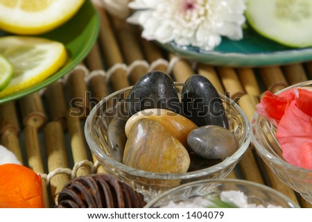 Hot massage rocks, surrounded by other spa objects. - stock photo