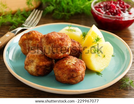 Hot meatballs with boiled potatoes and cranberry sauce .. - stock photo