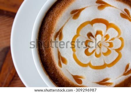 hot milk art coffee on wooden table , Vintage latte art coffee - stock photo