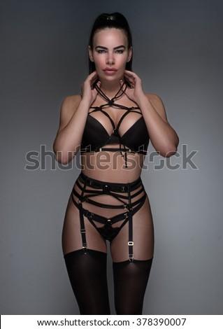 Hot model posing in tempting black lingerie set on grey - stock photo