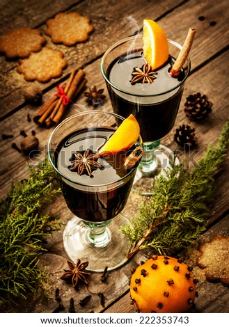 Hot mulled wine in a glass with orange slices, anise and cinnamon on vintage wood table. Christmas or winter warming drink with recipe ingredients around. - stock photo