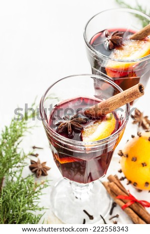 Hot mulled wine in a glass with orange slices, anise and cinnamon sticks on white background. Christmas or winter warming drink with recipe ingredients around. Layout with free text space. - stock photo