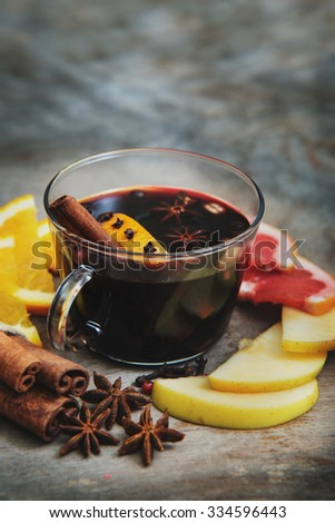 Hot mulled wine with cinnamon, slice of orange, anise and other spices. Winter and Christmas  traditions. Shallow dof. - stock photo