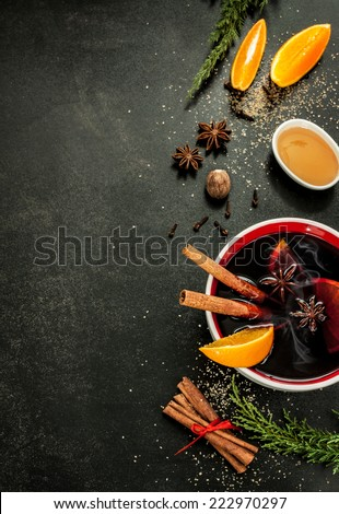 Hot mulled wine with orange slices, anise and cinnamon sticks on black chalkboard from above. Christmas or winter warming drink with recipe ingredients around. Layout with free text space. - stock photo