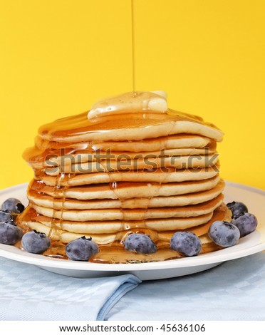 Hot pancake staked with blueberry fruit on a yellow background. Melted butter on the top with maple syrup falling on it. - stock photo