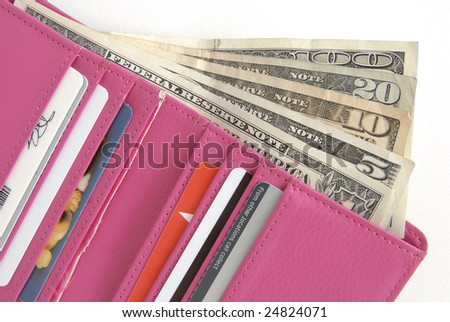 Hot Pink wallet is filled with credit cards and lots of cash, on a white background. - stock photo