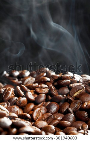 Hot roasted coffee beans and steam on black - stock photo