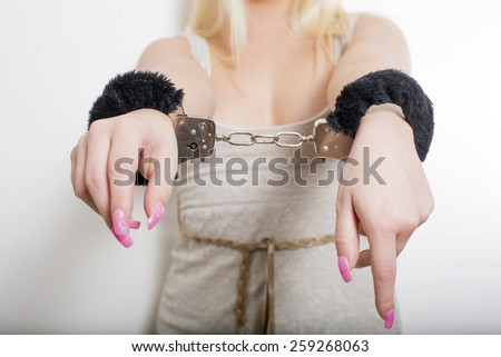 Hot sexy woman with string shirt and black handcuffs in studio - stock photo