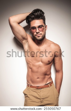 Hot sexy young man leaning on a white wall while holdinh one hand on his heair and the other one in his pocket. - stock photo