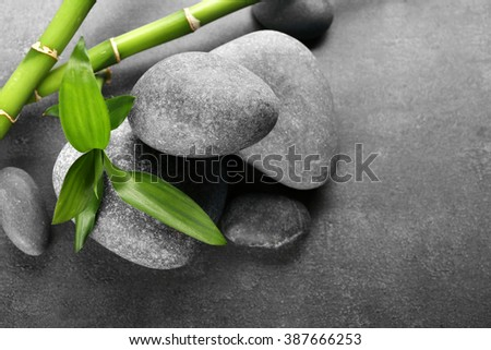 Hot spa stones with bamboo on grey background, close-up - stock photo