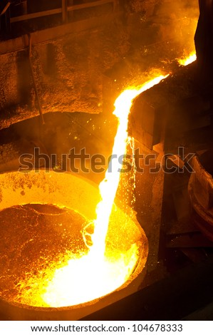Hot steel is poured into another pan - stock photo