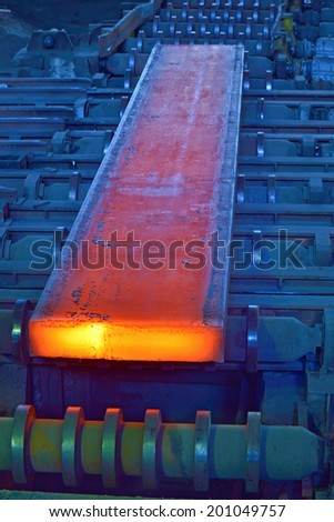 hot steel on conveyor inside of steel plant - stock photo