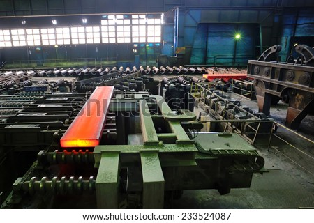 hot steel plate on conveyor inside of steel plant - stock photo