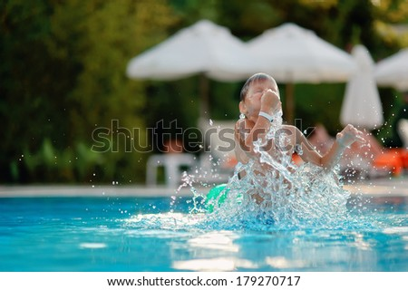 hot summer day, the boy dives and swims in the pool with turquoise water - stock photo
