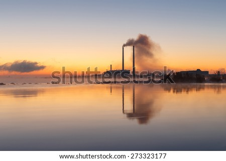 Hot sunset over the thermal power plant in winter - stock photo