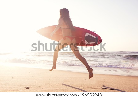Hot surfer girl running in the beach with her surfboard at sunset - stock photo