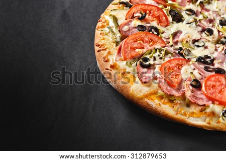 hot tasty delicious rustic homemade american pizza with tomato gherkin salami olives   with thick crust on black table - stock photo