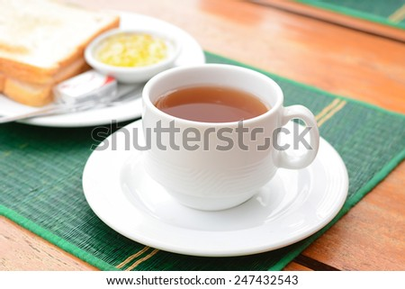 Hot tea in white cup with sliced bread over green mat  - stock photo