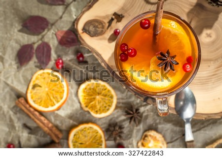 Hot tea with orange and cranberry on wooden board on black background - stock photo