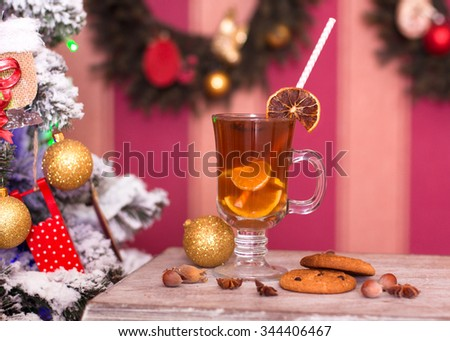 Hot tea with spices on old table on Christmas background - stock photo