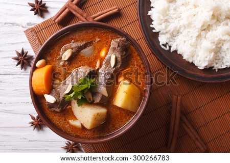 Hot traditional Thai beef massaman curry with peanuts and rice side dish close up. horizontal view from above - stock photo