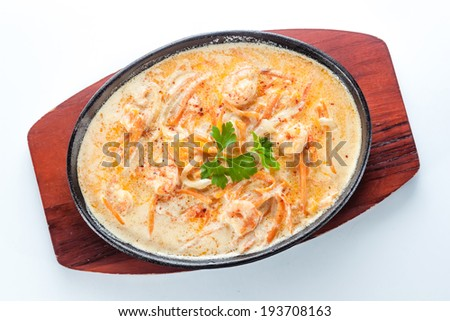 hot tray with chicken and carrots on a wooden plate - stock photo