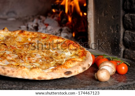 Hot Tuna pizza with oven fire on background  - stock photo