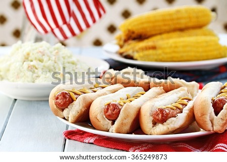 Hotdogs with Mustard, cole slaw and corn on a cob at a 4th of July BBQ picnic. - stock photo