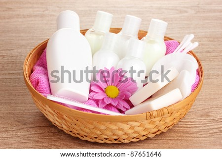 Hotel amenities kit in basket on wooden background - stock photo