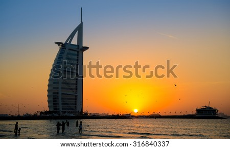 Hotel Burj Al Arab, Dubai in sunset with people in the water - stock photo