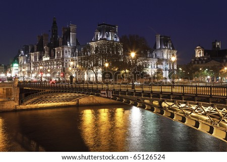 Hotel de Ville (City Hall of Paris)  and bridge D'Arcole across Seine river at night, Paris, France - stock photo