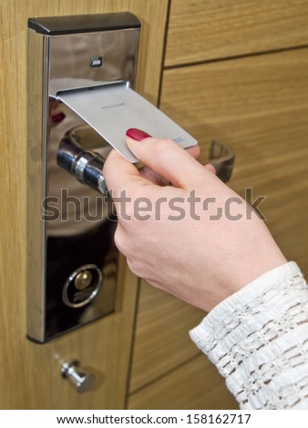 Hotel door - woman's hand inserting key card in an electronic lock - stock photo