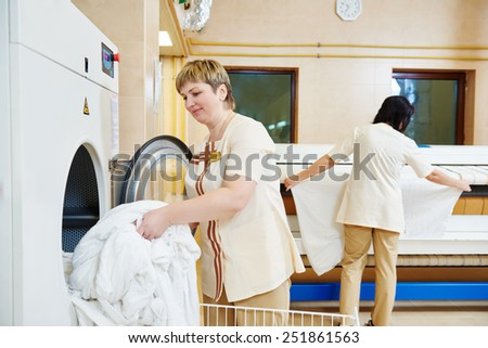 Hotel linen cleaning services. Woman operating with industrial washing machine  - stock photo