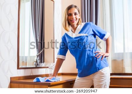 Hotel maid dusting - stock photo