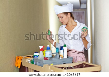 Hotel maid working with cleaning cart and cleaning supplies - stock photo