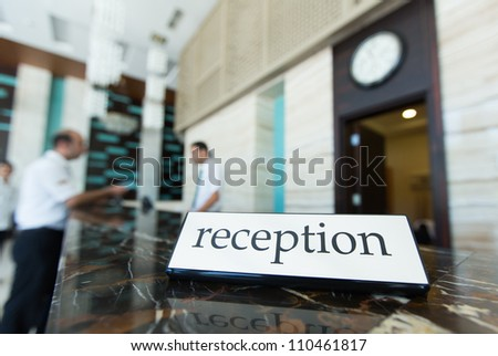 Hotel reception desk with a table and receptionists on a background - stock photo