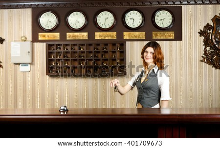 Hotel reception. Female receptionist at reception gives key to a guest. Modern hotel reception counter desk with bell. Woman receptionist at desk. Travel, hospitality, hotel booking concept.  - stock photo