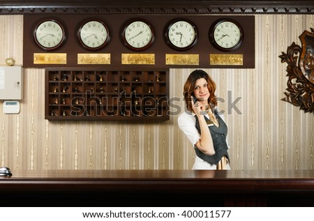 Hotel reception. Female receptionist at reception. Modern hotel reception counter desk with bell taking a call. Woman receptionist, concierge with phone. Travel, hospitality, hotel booking concept.  - stock photo