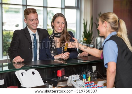 Hotel receptionist handing over key to two customers - stock photo