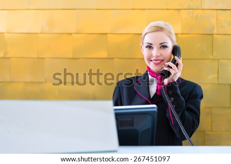 Hotel receptionist with phone on front desk - stock photo
