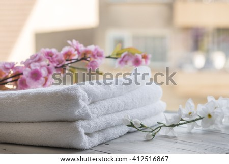 Hotel, resort, spa or luxury concept - Beauty and wellness - Towels and orchid against a sunny background.  - stock photo
