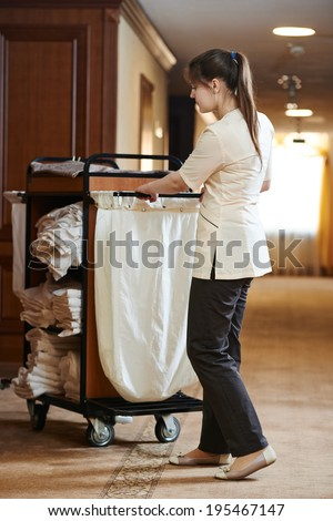 Hotel room service. female housekeeping worker with bedclothes linen in cart - stock photo