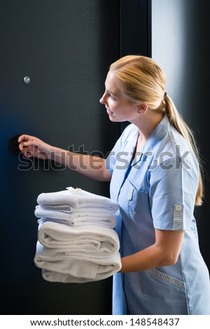 Hotel room service - young chambermaid standing in front of a room door in a suite with fresh towels - stock photo