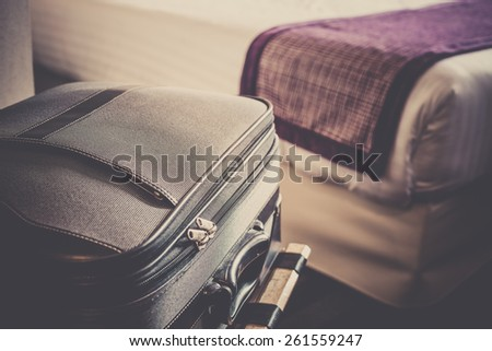 Hotel room with a suitcase on the luggage place and the bed. Filtered shot - stock photo
