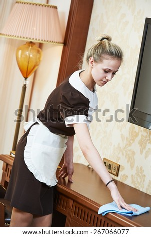 Hotel service. female housekeeping worker cleaning table from dust in room - stock photo
