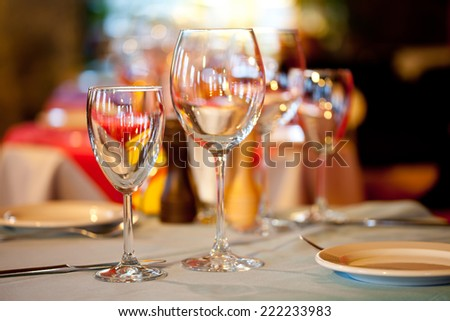 Hotel service: table in a restaurant with a white tablecloth, red napkins, wine glasses and cutlery. - stock photo