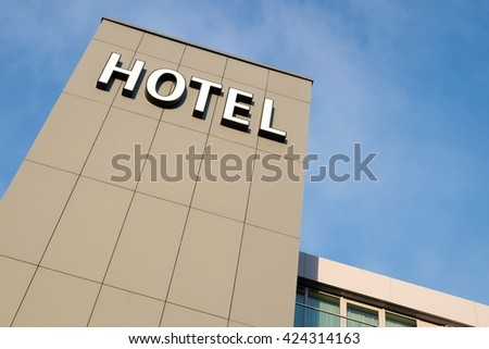 hotel sign against blue sky - stock photo